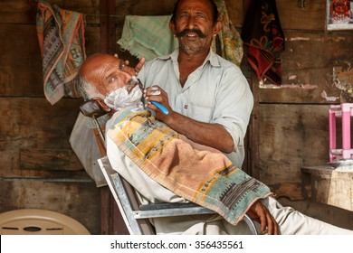 Jaisalmer,India - November 9, 2014:  Unidentified barber man uses razor blade and shaves beard of an elderly man in a barber shop in rural areas of Jaisalmer,India