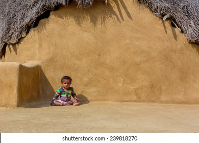 JAISALMER,INDIA - November 9,2014 : Unidentified child sits and crawls in front of the house made with mud and thatch in Khuri village,Jaisalmer,India