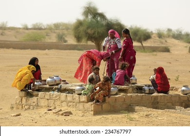 JAISALMER,INDIA - November 9,2014 : Unidentified women draw water form the well and take it to their home in rural ares of Jaisalmer,India.