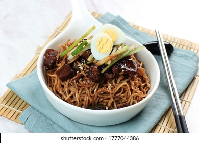 Jajangmyeon or JJajangmyeon Korean Noodle with Black Bean Sauce, Served with Cucumber and Sesame Seed