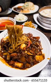 jajangmyeon, Korean black noodle with spicy chicken, onion and dried chili on a white plate
