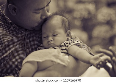 JAKARTA 2017 - Portrait of father kissing his daughter in a garden during hot sunny day on January