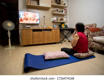 Jakarta , DKI Jakarta / Indonesia - May 7 2020 : People Doing Vesak Day Prayer at home by live streaming because of the Corona Virus Pandemic