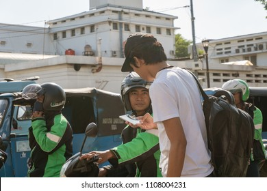 Jakarta / Indonesia - 1 June 2018: A man picked up by this online ojek driver in front of Kota Train Station.