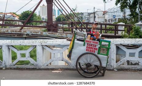 Jakarta / Indonesia 25 Dec. 2018: Indonesian man sells meatballs from his pushcart on a bridge.
