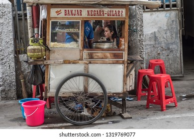 Jakarta / Indonesia 27 Dec.2018: Indonesian young woman sits a a food pushcart in a street.