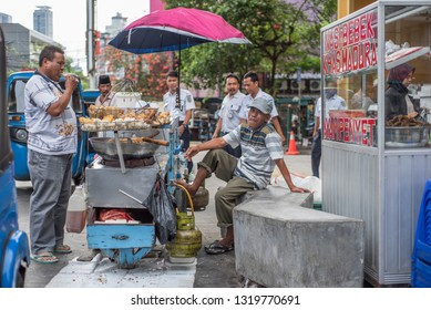 Jakarta / Indonesia 27 Dec.2018: Indonesian man smiles at the camera while a customer eats at his pushcart on a street.
