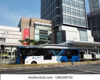 Jakarta, Indonesia - April 17, 2019: TransJakarta bus getting some passengers at Bundaran HI bus shelter on Thamrin street.