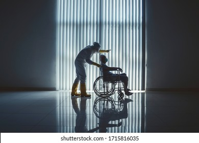 JAKARTA, Indonesia - April 23, 2020: Doctor with hazardous materials suit pushing an elderly patient in wheel chair infected with coronavirus in Jakarta Hospital