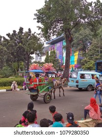 Jakarta, Indonesia - April 28, 2018: A traditional Jakarta's horse-drawn carriage is walking around the city carrying the coachman and looking for passengers.