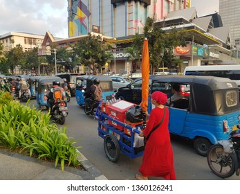 Jakarta, Indonesia - April 5 2019: Auto rickshaw, called Bajaj, and a woman pushing a food cart in the very crowded streets of Jakarta, Indonesia capital city.
