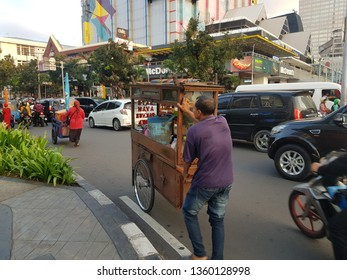 Jakarta, Indonesia - April 5 2019: A man pushing a food cart, called Kaki lima, in the crowded streets of central Jakarta in Indonesia capital city