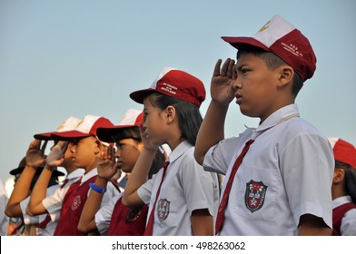 Jakarta, Indonesia - August 17, 2014: Indonesian elementary school students with red and white uniform saluted at ceremony of Independence Day of Indonesia in Jakarta, Indonesia.