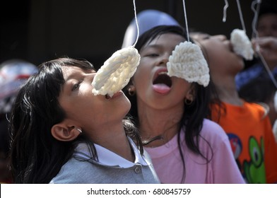 Jakarta, Indonesia - August 17, 2014: Little child are following the race eating crackers in Indonesia's independence day celebrations at Kemang Street, Jakarta, Indonesia.