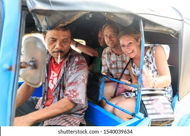 JAKARTA, INDONESIA - AUGUST 2, 2015: Tourists take a trip in a traditional auto rickshaw, aka tuktuk, in Jakarta, Indonesia, on August 2, 2015