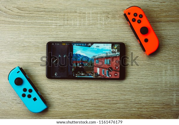 Jakarta, Indonesia - August 22, 2018: The Xiaomi Redmi Note 5 smartphone and Joy-Con controller Nintendo Switch, playing PUBG Mobile games.