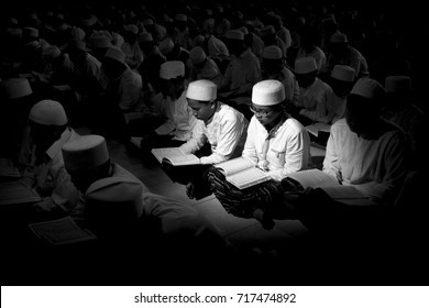 JAKARTA, INDONESIA - AUGUST 26, 2016 :  Muslim students.  the santri are reading the holy book of the Qur'an in the middle of the night. black and white filter. Muslim lifestyle.