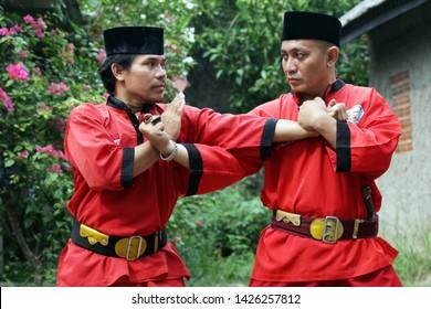 Jakarta, Indonesia - December 01, 2015 : Betawi Pencak Silat Indonesian traditional martial art performing pencak silat combat techniques in outdoor.