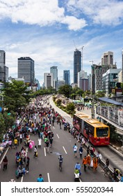 JAKARTA, INDONESIA - DECEMBER 18, 2016: People enjoy outdoor activities during the car free day held every Sunday morning in the business district of Jakarta. Only Transjakarta bus can run.