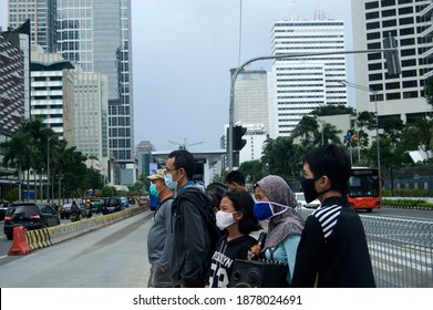 JAKARTA, INDONESIA - DECEMBER 18, 2020: People wear face masks while waiting to cross roads in a business district in Jakarta, Indonesia on 18 December 2020. Indonesia reached 650,000 cumulative cases
