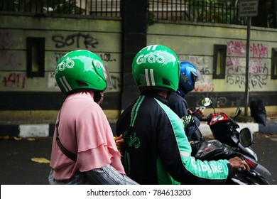 Jakarta, Indonesia - December 28 2017: Grab Bike Riders on Street. Grab is a technology company that offers wide range of ride-hailing and logistics services through its app in Southeast Asia
