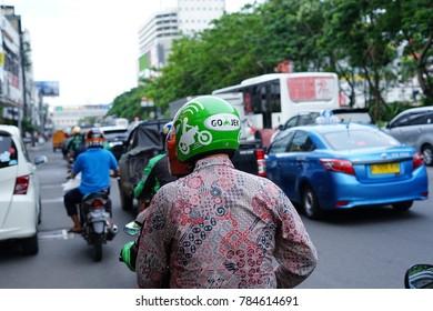 Jakarta, Indonesia - December 28 2017: Bike passengers wearing Helmet with Gojek Logo. Gojek is Indonesian transportation startup