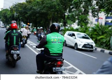 Jakarta, Indonesia - December 28 2017: Gojek Driver wearing Jacket with Gojek Logo side by side with grab driver. Gojek is Indonesian transportation startup