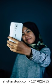 Jakarta, Indonesia - December 5, 2018:  The woman taking selfie with Nokia 6.1 Plus smartphone .