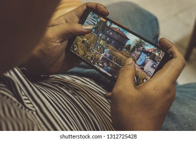 Jakarta, Indonesia - February 14, 2019: The man playing a PUBG Mobile on Asus ROG Phone gaming smartphone.