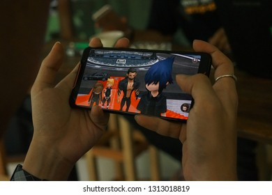 Jakarta, Indonesia - February 14, 2019: The man playing a Final Fantasy XV Pocket Edition on Asus ROG Phone gaming smartphone.