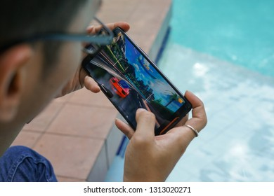 Jakarta, Indonesia - February 14, 2019: The man playing an Asphalt 9: Legends action racing game on Asus ROG Phone gaming smartphone.