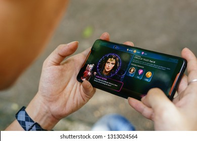 Jakarta, Indonesia - February 14, 2019: The man playing an Injustice 2 on Asus ROG Phone gaming smartphone.