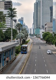 Jakarta, Indonesia - February 16, 2019: TransJakarta bus passing through Jalan Thamrin (Thamrin street).