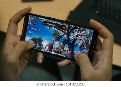 Jakarta, Indonesia - February 17, 2019: Playing a PUBG Mobile battle royale games on Asus ROG Phone gaming smartphone.