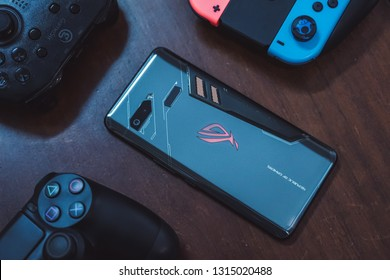 Jakarta, Indonesia - February 17, 2019: The back of Asus ROG Phone gaming smartphone with Joy-Con controller, DualShock 4, and GameSir T4.