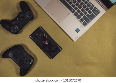 Jakarta, Indonesia - February 17, 2019: The back of Asus ROG Phone gaming smartphone with GameSir T4 controller, DualShock 4 and laptop.