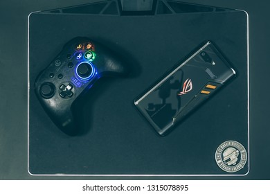 Jakarta, Indonesia - February 17, 2019: The back of Asus ROG Phone gaming smartphone with GameSir T4 wireless controller.