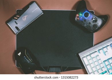 Jakarta, Indonesia - February 17, 2019: The back of Asus ROG Phone gaming smartphone with GameSir T4 controller, keyboard and mouse.
