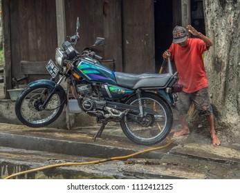 Jakarta,  Indonesia - February 20, 2018: Local man washing the motorcycle (ojek) on the street of Jakarta.