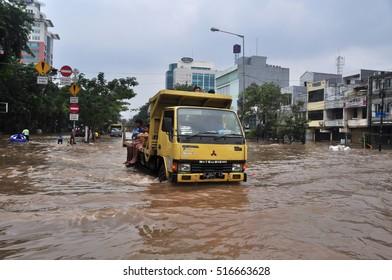 Jakarta, Indonesia - February 4, 2014 : Jakarta resident across the flooding street on vehicle in Kampung Melayu, Jakarta, Indonesia.