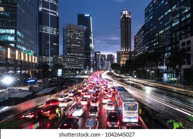 Jakarta, Indonesia - February 8 2018: Cars, buses and other vehicles stuck in a traffic jam in the main business district avenue at night in Jakarta, Indonesia capital city.
