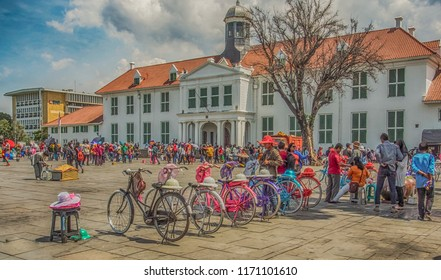 Jakarta, Indonesia - January 11, 2015: Coloured bikes and people in colourful costumes at Fatahillah Square in Jakarta