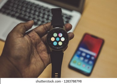 Jakarta, Indonesia - January 14, 2019: The Samsung Galaxy Watch smartwatch with Realme C1 Android smartphone and laptop.