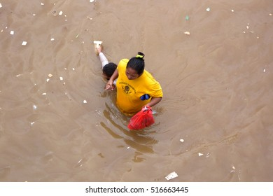 Jakarta, Indonesia - January 18, 2014 : A mother with a child crossing flooded roads caused by heavy rains and overflowing rivers in Kampung Melayu, Jakarta, Indonesia.