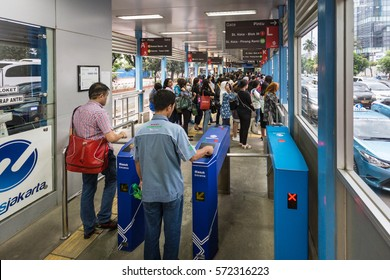 JAKARTA, INDONESIA - JANUARY 27, 2017: People enters a Transjakarta bus shelter, where buses travel on a separate traffic lane and avoid Jakarta heavy traffic jams.