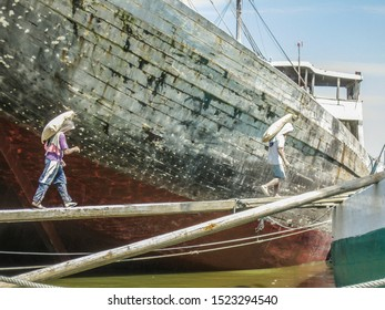Jakarta, Indonesia - July 13, 2009: unskilled workers loading sacks with cement onto a wooden transport vessel4