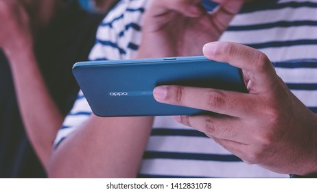 Jakarta, Indonesia - June 1, 2019: The man playing mobile games on OPPO Reno 10x Zoom Android smartphone.