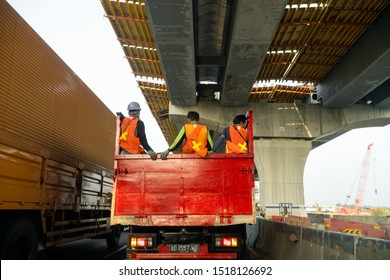 Jakarta, Indonesia - June 17, 2019: Construction workers hitchhike truck on highway, Indonesia.
