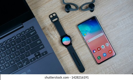 Jakarta, Indonesia - June 19, 2019: Samsung Galaxy Watch Active smartwatch with Samsung Galaxy S10+ flagship Android smartphone, laptop, and eartphone wireless.