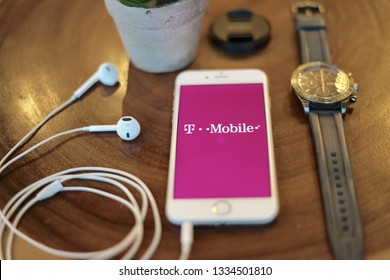 Jakarta, Indonesia - March 10 2019: T Mobile Logo Iphone Screen on the Table with men watch and earphone